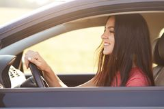 De foto van opgetogen blije donkerbruine vrouwelijke bestuurder bekijkt gelukkig voorruit, houdt handen op wiel, drijft snelle au stock fotografie