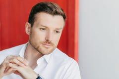 De foto van peinzende mannelijke ondernemer ziet zorgvuldig eruit opzij, houdt handen tgether, gekleed in elegant wit overhemd, d stock afbeelding