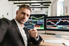De foto van unshaved de mens die selfie terwijl het werken in bureau aan computer met grafiek en grafieken bij het scherm nemen stock fotografie