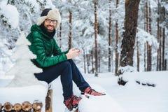 De foto van vrolijke mannelijke typesberichten op smartphone kijkt direct in camera, zit in wit de winterbos, gelukkig glimlacht, royalty-vrije stock foto