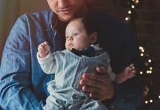 De foto van weinig zuigeling in vader ` s overhandigt dichtbij een venster stock foto