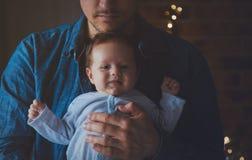 De foto van weinig zuigeling in vader ` s overhandigt dichtbij een venster stock afbeelding