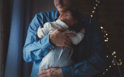 De foto van weinig zuigeling in vader ` s overhandigt dichtbij een venster royalty-vrije stock foto's