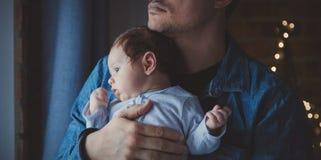 De foto van weinig zuigeling in vader ` s overhandigt dichtbij een venster stock afbeeldingen