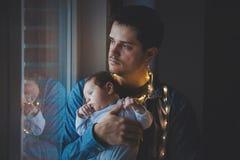 De foto van weinig zuigeling in vader ` s overhandigt dichtbij een venster royalty-vrije stock fotografie