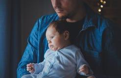 De foto van weinig zuigeling in vader ` s overhandigt dichtbij een venster royalty-vrije stock foto
