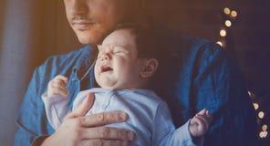 De foto van weinig zuigeling in vader ` s overhandigt dichtbij een venster royalty-vrije stock afbeelding