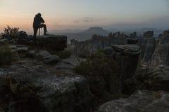 De fotograaf bevindt zich op de rand die van de klip, op zonsopgang in Saksisch Zwitserland in de herfst wachten Royalty-vrije Stock Afbeelding