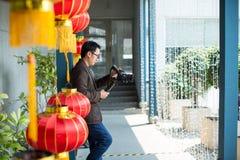 De fotograaf en de videomakermens houden DSLR-camera op zijn hand aan het maken van lengte stock foto