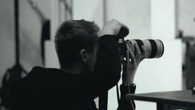 De fotograaf neemt een digitale camera in een fotostudio stock video