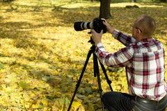De fotograaf neemt schot in de herfstpark Stock Afbeelding