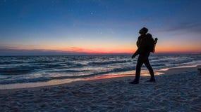 De fotograaf verkent uit de beste plaats voor de nacht neer te regelen stock foto