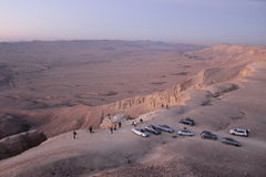 De fotografen bekijken de zonsondergang vanaf de bovenkant van Ramon Crater aan binnen het Stock Foto's