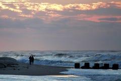 De fotografen schieten de golven tijdens een onweer bij zonsopgang Royalty-vrije Stock Foto