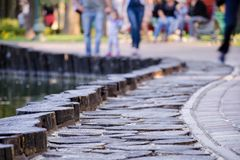 De-foyer ou photo brouillée avec des personnes marchant le long du trottoir pavé en parc photographie stock