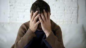 de 24 fpsvideo schoot dicht op de jonge mens die thuis gedeprimeerd kijken stock video