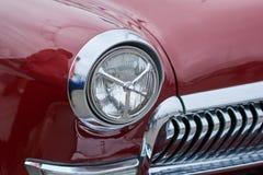 De främre ljusen av en gammal röd bil Royaltyfri Foto