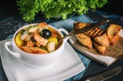 De Franse Bouillabaissen van de vissensoep met zeevruchten, zalmfilet, garnalen, rijk aroma, heerlijk diner in een mooi wit stock afbeeldingen