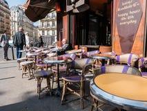 De Franse heer leest het avonddocument bij een stoep caf van Parijs Stock Foto's