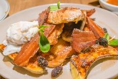 De Franse toost met bacon, stroopte ei, geroosterde banaan en bessen Stock Foto's