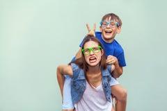 De freckled broer beklom omhoog op de rug van een oudere leuke zuster Het maken van grappig gek gezicht en het bekijken camera stock fotografie