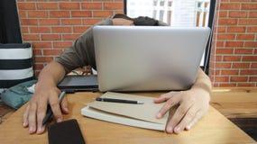 De freelance Aziatische slaap van de mensenarbeider op laptop met smar notitieboekje, Royalty-vrije Stock Afbeelding