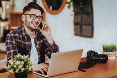 De Freelancerbesprekingen telefoneren terwijl het Werken aan Laptop royalty-vrije stock foto's