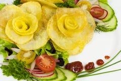 De frieten in de vorm van namen op een plaat met een salade toe Royalty-vrije Stock Afbeeldingen