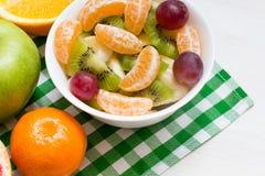 De fruitsalade met smakelijke vruchten op de witte plaat, gezond concept, sluit omhoog stock foto