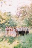 De fulla-hight fotona av nygift personparen, de bästa männen och brudtärnorna som rymmer buketterna av de rosa blommorna i Royaltyfri Fotografi