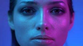 De futuristische mannequin met schittert make-up in kleurrijke neonlichten die langzaam en haar ogen in studio bewegen knipperen stock video