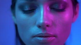 De futuristische mannequin met schittert make-up in kleurrijke neonlichten die vastbesloten en op haar ogen in studio letten slui stock footage