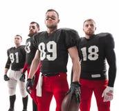 De fyra amerikanska fotbollsspelarna som poserar med bollen på vit bakgrund Royaltyfri Foto