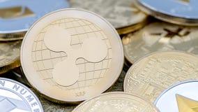 De fysieke munt van metaal gouden Ripplecoin over anderen muntstukken Rimpelingsmuntstuk stock foto