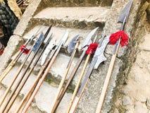 De gamla forntida medeltida kalla vapnen, yxor, hillebarder, knivar, svärd med trähandtag slickar på stenmomenten av slotten arkivbilder