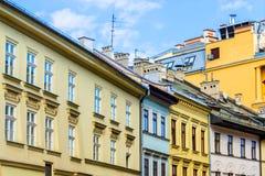 De gamla historiska hyreshusarna på den gamla marknadsfyrkanten i Cracow, Polen Arkivfoton