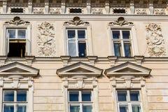 De gamla historiska hyreshusarna på den gamla marknadsfyrkanten i Cracow, Polen Arkivfoto