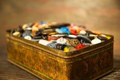 De gamla knapparna Knappar i en gammal metallask Royaltyfri Bild