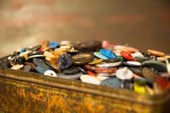 De gamla knapparna Knappar i en gammal metallask Arkivbilder