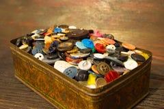 De gamla knapparna Knappar i en gammal metallask Arkivfoto