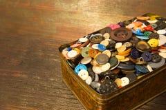 De gamla knapparna Knappar i en gammal metallask Royaltyfri Foto