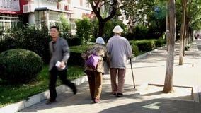 De gamla paren går på gatan