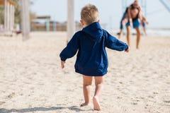 De gang van de babyjongen op de strand achtermening royalty-vrije stock afbeeldingen