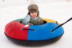 De gang van de winter, jongen berijdt een sneeuw-Buizenstelsel royalty-vrije stock afbeeldingen