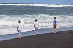 De gang van drie tienerjongens langs een zwart vulkanisch strand stock fotografie