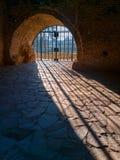 De gang van het boogfort van koude vochtige Zwartheid om te gloeien Licht met de geroeste cel van de ijzerrooster Gevangenispoort stock fotografie