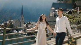 De gang van het uitstekende geklede paar langs de brug bij de achtergrond van de oude stad in de bergen stock videobeelden
