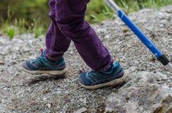 De gang van kind` s voeten langs de bergweg Stock Afbeelding