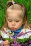 De gangen van het meisje in de lente op een jong gras Stock Afbeelding