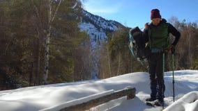 De gangen van de reizigerskerel op sneeuwschoenen in de winter in de bergen Hij zit op een houten bank om te rusten